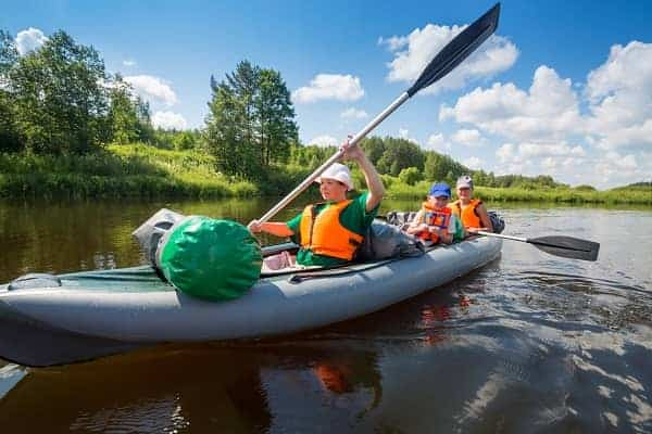 Two women with oars and little boy sail on inflatable boats