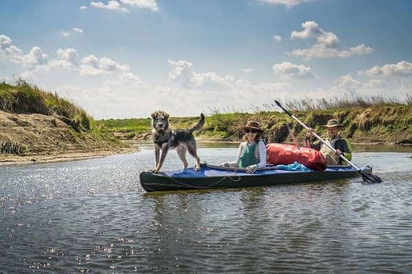 Man and woman with a dog on a river trip on a kayak